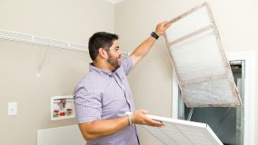 Man with dark hair replacing the air filter in a Clayton Built® home.