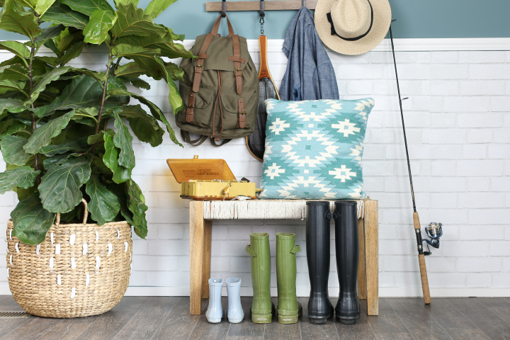 Manufactured home entryway with colorful accent pillow and fishing gear.