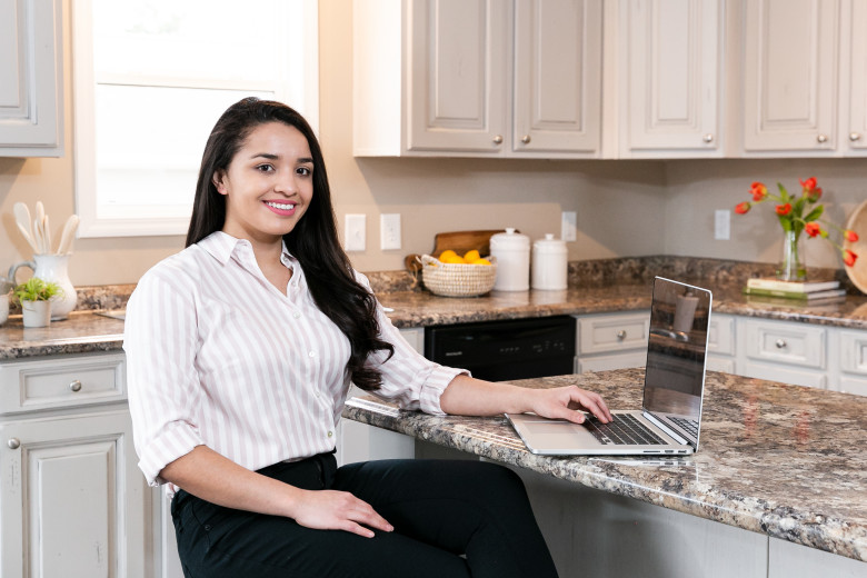 A woman sitting at a kitchen island in a clayton home using a laptop.