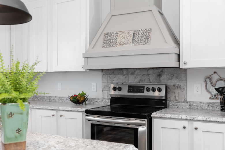 The kitchen of the Palmetto model with black appliances, white cabinets and a large gray range hood.
