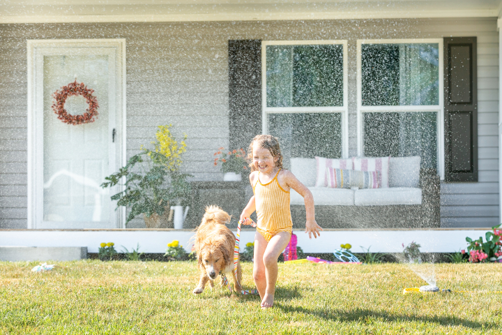 Child and dog playing in the sprinkler outside their manufactured home.