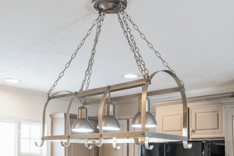Large hanging silver chandelier with pot and pan hooks.