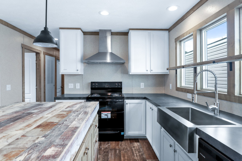 Manufactured home kitchen with large windows and stainless-steel features.