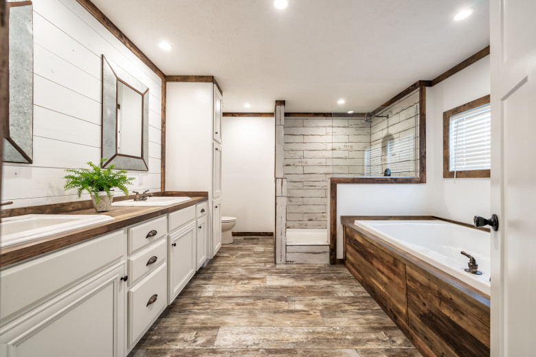 Primary bathroom of the Avalyn with large soaker tub, walk-in shower and white cabinets.