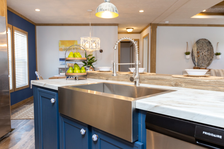 Kitchen of the Kimmel model, with blue cabinetry, white marbled countertops and a stainless steel farmhouse sink.