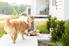Girl plays with dog outside a manufactured home.