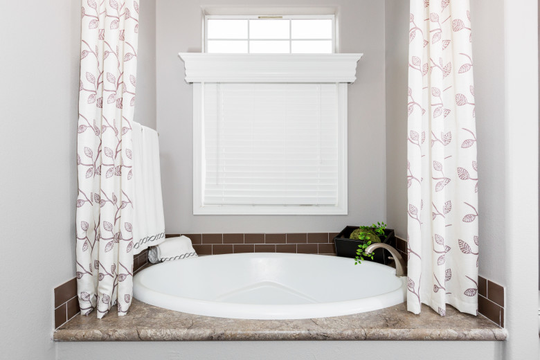 A round sunken garden tub in a manufactured home bathroom with a window and storage space around it.