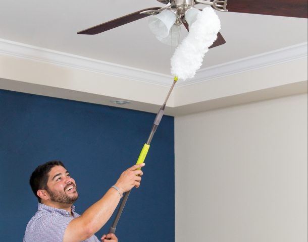 Man dusting a ceiling fan in a manufactured home.