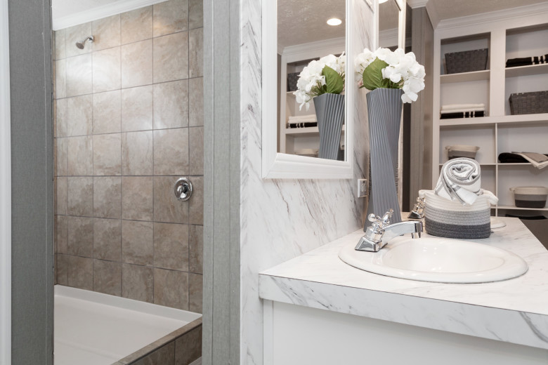 White manufactured  home bathroom with clean countertops and flowers by the sink.