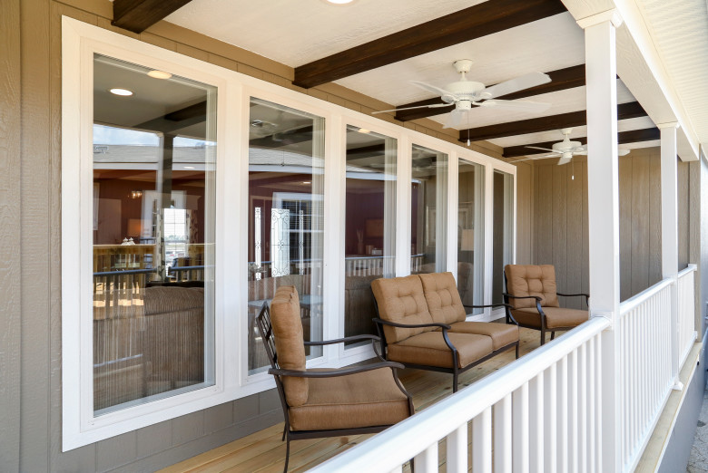 Outdoor patio area with two ceiling fans and comfortable seating.