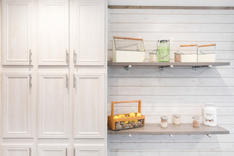 2 light wood shelves with assorted jars and baskets on a cream shiplap wall with cream cabinets to the left of it.