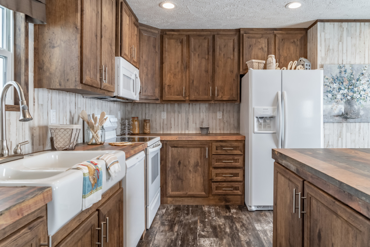 The wooden cabinetry and rustic wallpaper in the kitchen of The Locker Room model by Clayton.