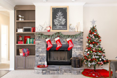 Living area of manufactured home with fireplace feature decorated with stockings and Christmas tree.