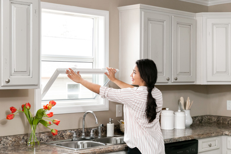 A person cleaning a window in their manufactured home kitchen with white cabinets and stone style counter tops.