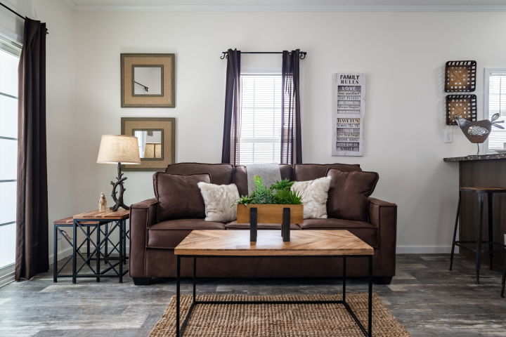 Livingroom of the Elite model with a brown leather couch and other modern décor.