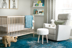 A nursery is decorated with a light wood crib, a blue rug, a white glider chair and shelves with colorful baby books.
