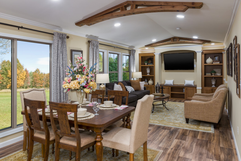 Manufactured home with maple stained ceiling beams and large glass doors.