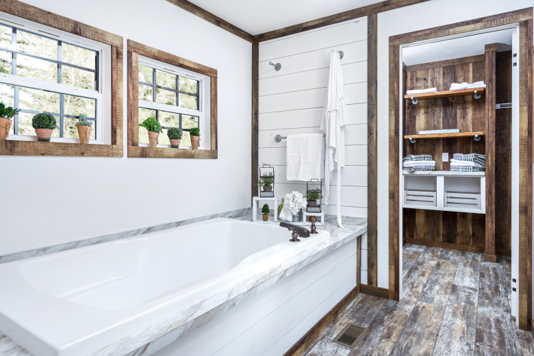 A manufactured home bathroom that has a large bathtub surrounded by shiplap and marble accents.