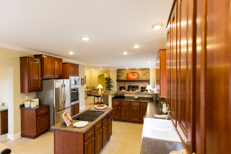 Manufactured home kitchen with maple stained cabinetry and stainless steel appliances.