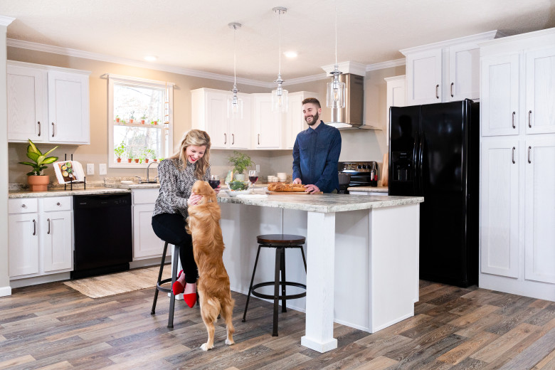 Couple standing in a Clayton Built® home kitchen with their dog.
