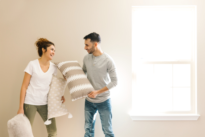 Couple holding pillows inside a new, empty manufactured home.