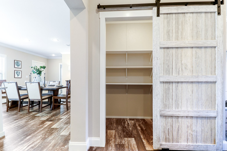 The walk-in pantry of the Clayton Built® home, The Tahoe, that features a sliding barn door and several shelves inside.
