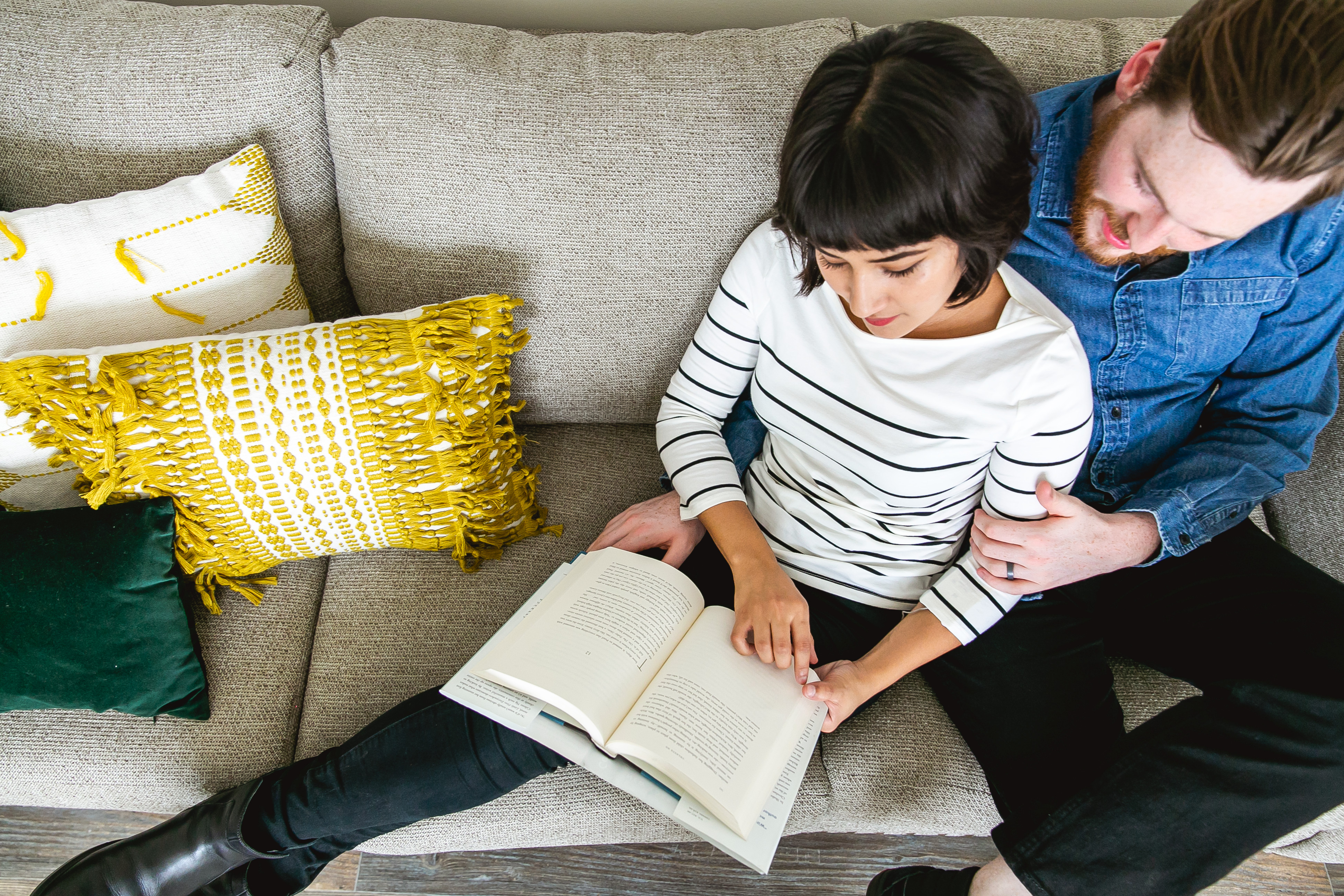 Couple cuddled up on the couch reading a book together in their manufactured home