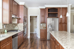 Manufactured home kitchen with wooden cabinetry and large breakfast bar.