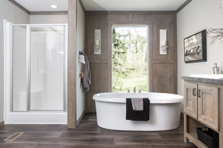 Free standing garden tub in front of a large floor to ceiling window and a walk-in shower of a manufactured home bathroom