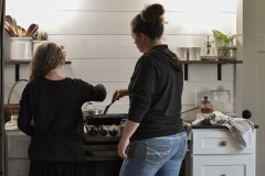 Mom and daughter cook together in farmhouse kitchen