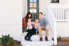 Family of four sitting in the stoop of a white porch.
