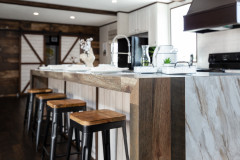 Manufactured home kitchen with large kitchen island with wood and marble detailing.