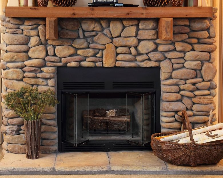modular home wood burning fireplace with stones and wood.