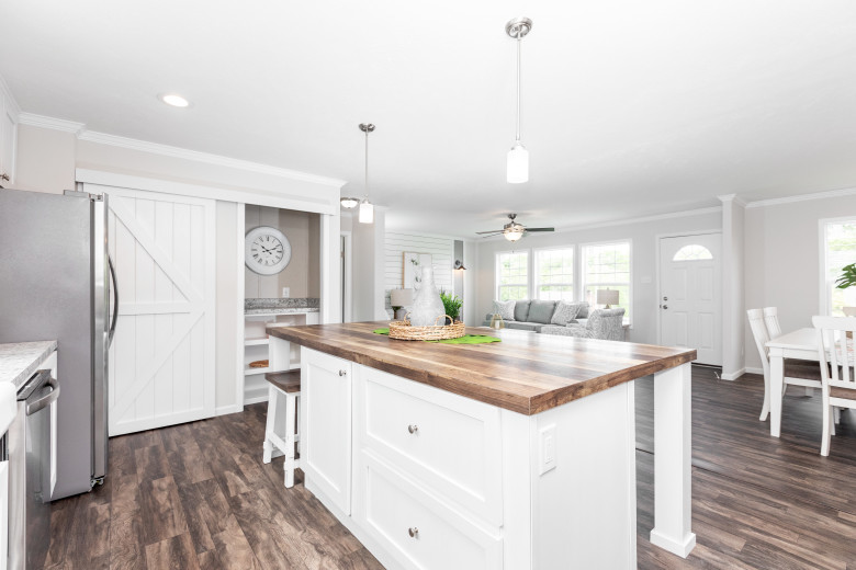 The kitchen of the Island Breeze model featuring sliding white barnwood doors to the pantry.