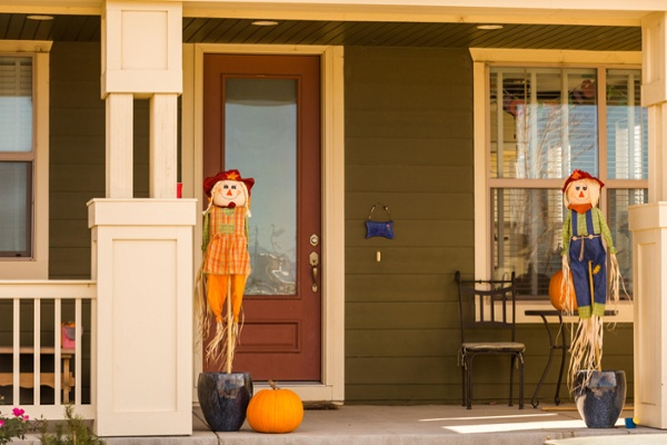 Scarecrows on front porch of home.