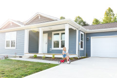 Exterior of a manufactured home with a child outside riding a bike.