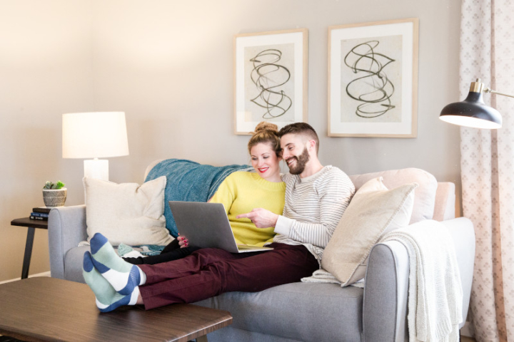 Woman in yellow sweater and man in striped shirt and red pants sit on a couch with pillows and blankets and look at a laptop.
