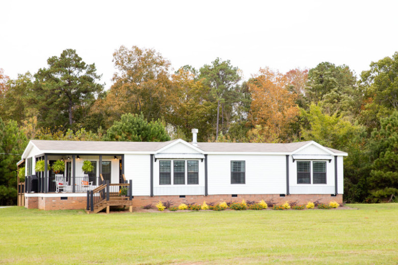 Manufactured home with white siding, red brick skirting and large side porch leading down to the lawn.