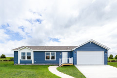 Exterior of manufactured home with blue siding and white doors and window trim.