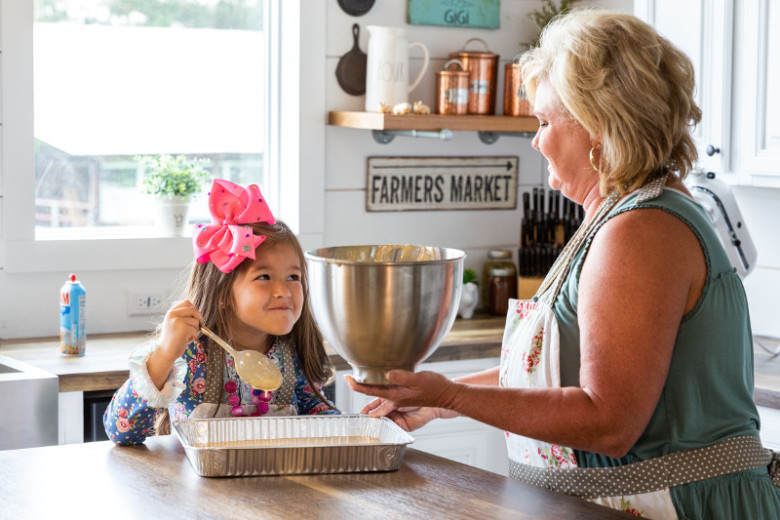 Woman and granddaughter backe inside a manufactured home kitchen decorated with farmhouse decor.