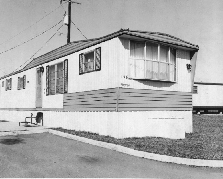Black and white photo of a mobile home with steps leading up to the door, bay window at the end and telephone pole behind it.