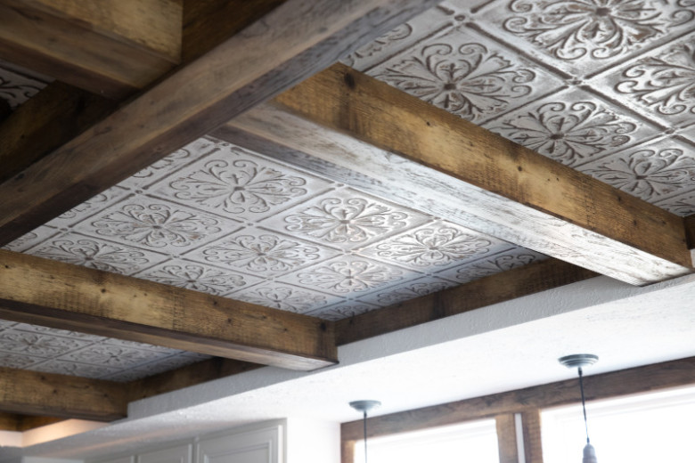Brown wooden ceiling beams with light brown and white metal tiles underneath.