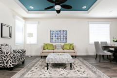 Living room of a manufactured home with blue accent ceiling and blue and green accent décor.