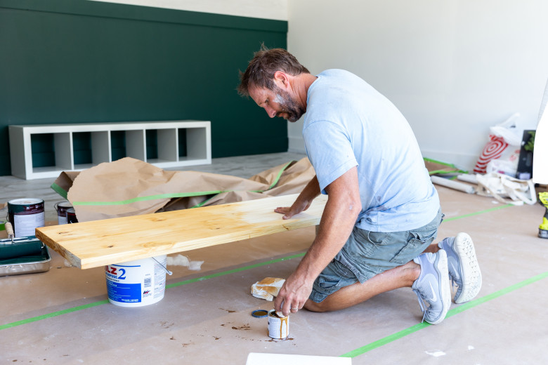 Man painting shelves in the garage of a manufactured home