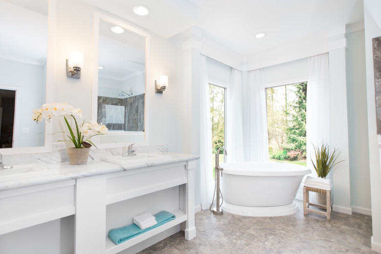Beautiful manufactured home primary bathroom showcasing white tub and large windows.