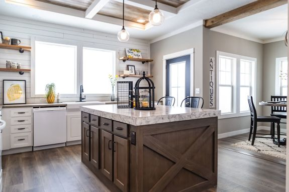 "The barn door style kitchen island accent piece surrounded by the bright white cabinets in the 1434 Carolina ""Southern Belle"" makes this a farm girl's dream home with eat-in dining room nearby."