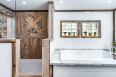 A separate rustic-style bathtub and walk-in shower featuring a wood wall in a manufactured home.