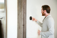 Person adjusting their ecobee thermostat in their manufactured home.