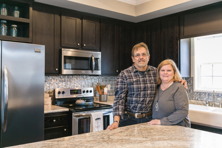 couple stands in prefab kitchen with metal backsplash