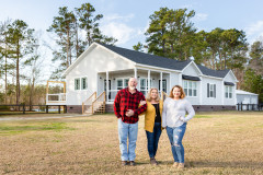 Family stands in front of their new farmhouse home built by Clayton Homes